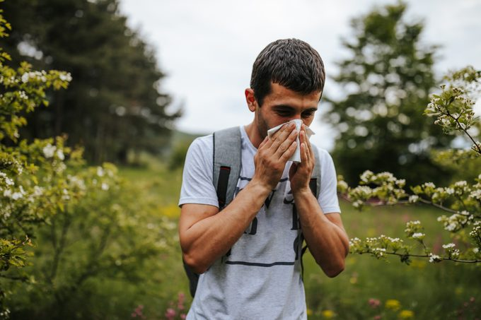 One young man sneezing in blooming nature on sunny spring day