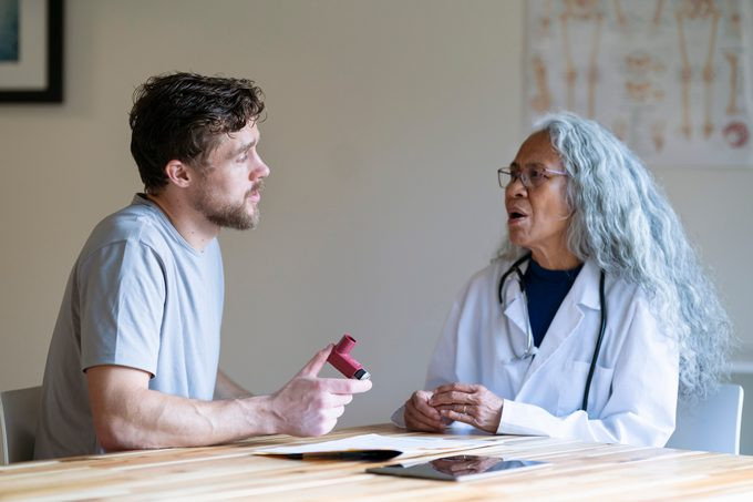 Man in medical consultation discusses with his doctor using a puffer inhaler for asthma