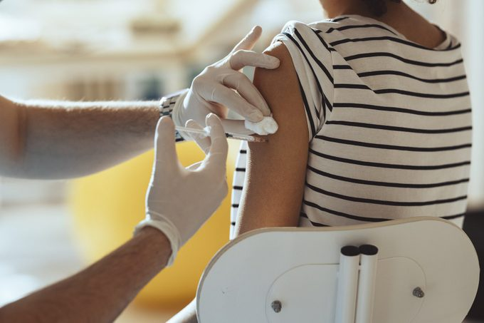 cropped shot of young woman getting injection in arm