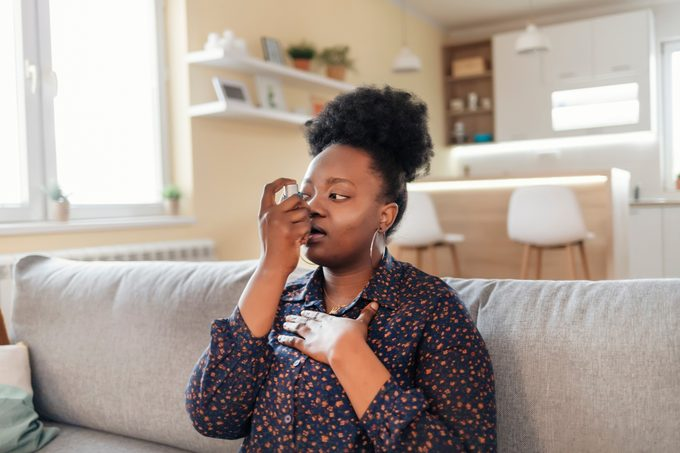 Young Woman With Inhaler Having Asthma Attack, Closeup