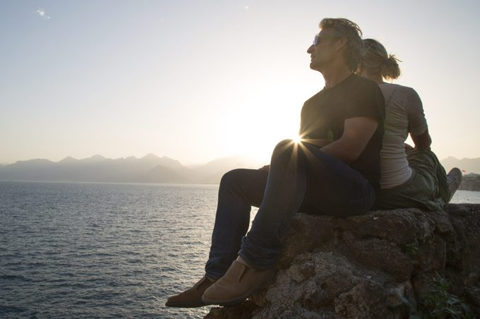 Couple sit on rock above sea, looking off
