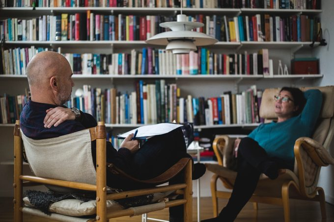 Male therapist discussing with female mature patient against bookshelf at home office