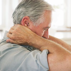senior man with neck pain at home
