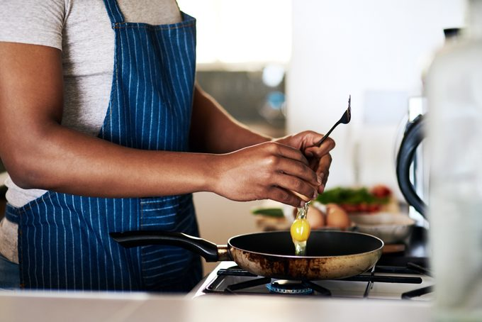 Cropped shot of an unrecognizable man frying eggs while making breakfast in his kitchen at home