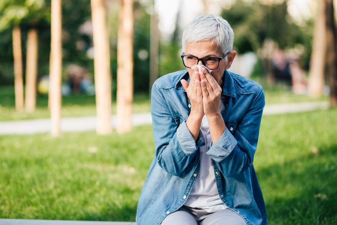 woman in park sneezing into a tissue