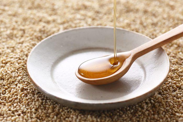 Pouring sesame oil into a small ceramic dish