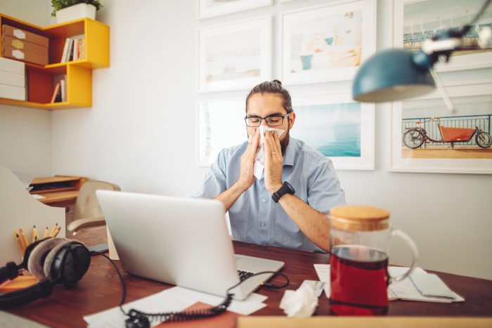man suffering from allergies while working from home
