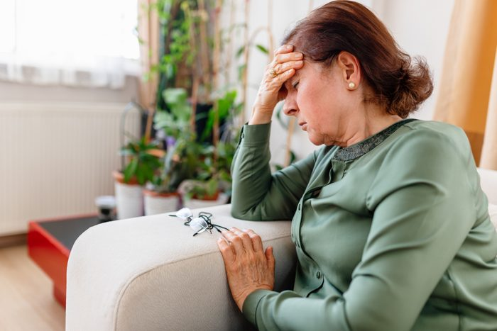 A Distraught Senior WoMan Suffering From a Migraine
