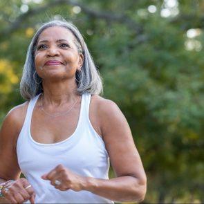 Senior woman jogging in public park