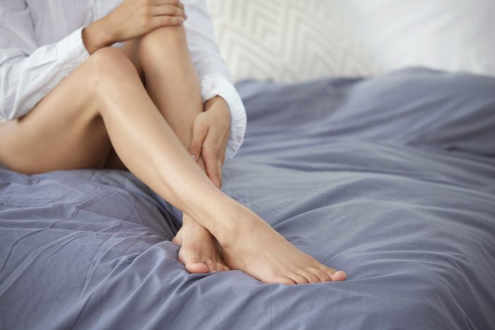 Cropped shot of an unrecognizable young woman rubbing her silky soft legs while sitting on her bed at home