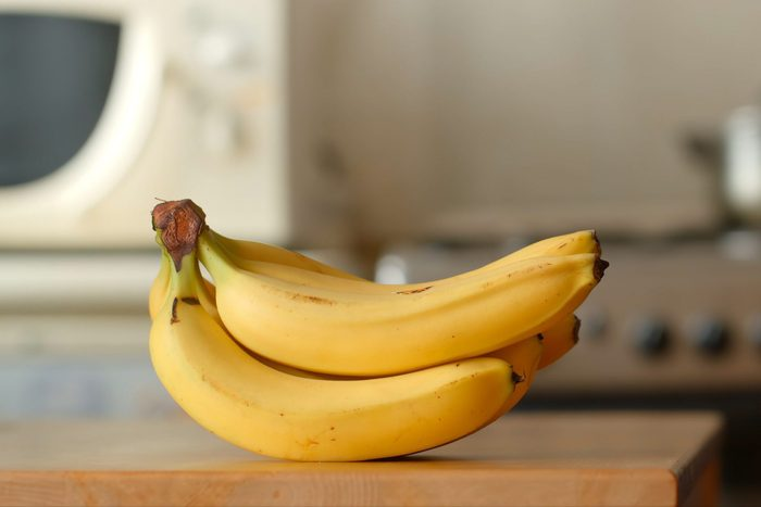 Bananas lie on a table in a kitchen