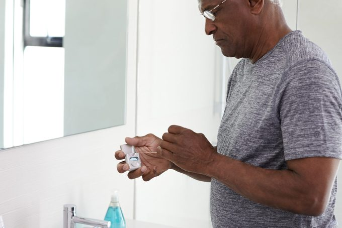 Senior Man Flossing Teeth Standing Next To Bathroom Mirror Wearing Pajamas