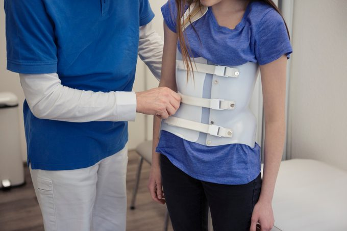 doctor helping child with scoliosis brace