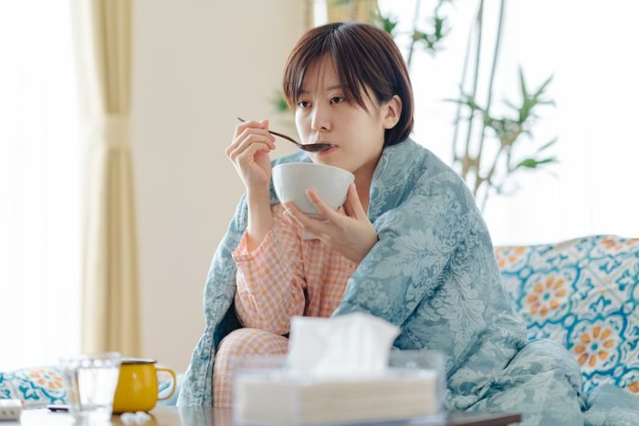 Sick woman having soup to recover