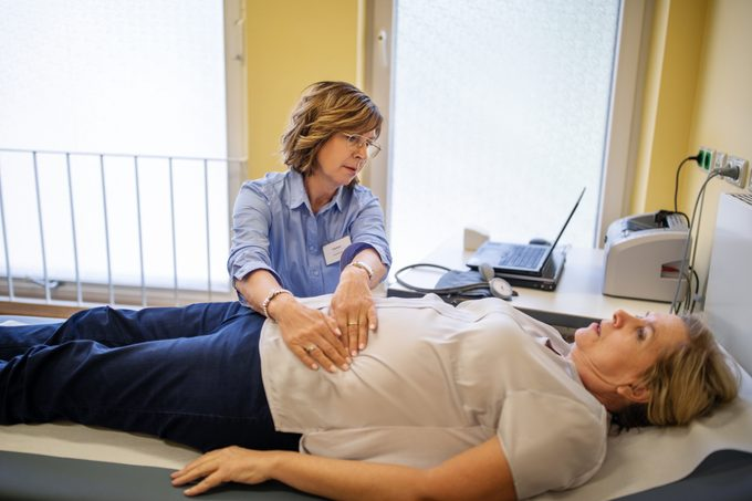Doctor checking patient's stomach in a clinic