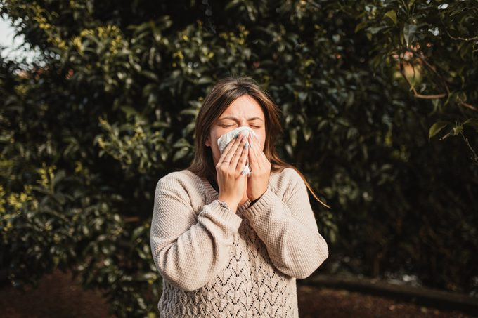 woMan sneezing from the cover disease after getting vaccinated