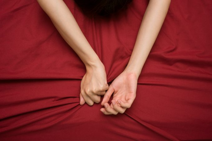 woman's hands on maroon colored bed sheets