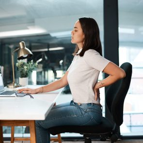 young woman suffering from back pain while sitting and working at desk in office