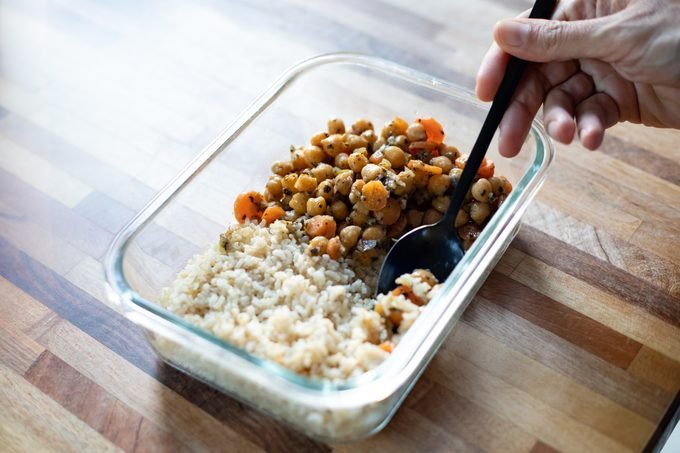person eating food leftovers from container