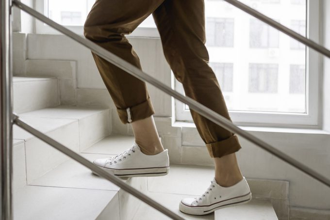 lower half of woman walking up stairs