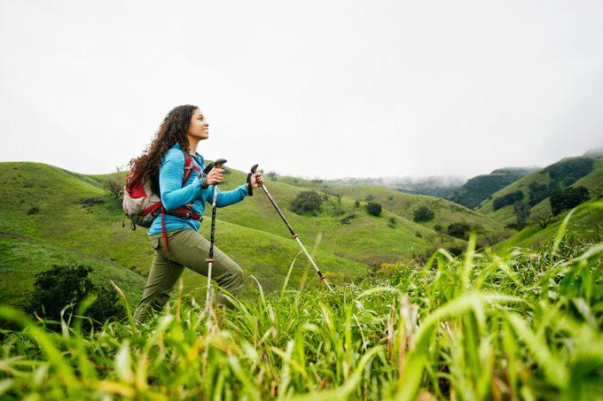 Smiling woman hiking with walking sticks